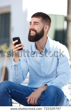 Portrait of handsome man sitting outside holding mobile phone #725509747