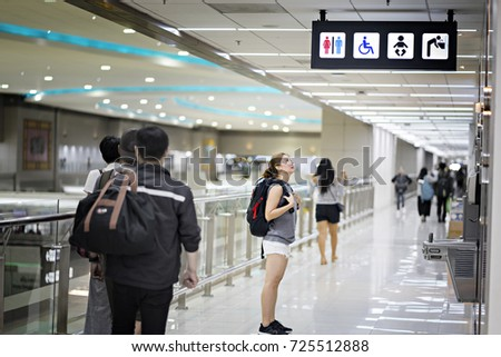 Young tourist girl looking the  toilet sign.entrance to the male and female toilet. Sign in airport