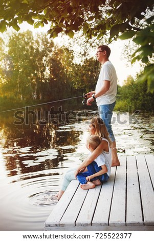Young happy family with kids fishing in pond in summer #725522377