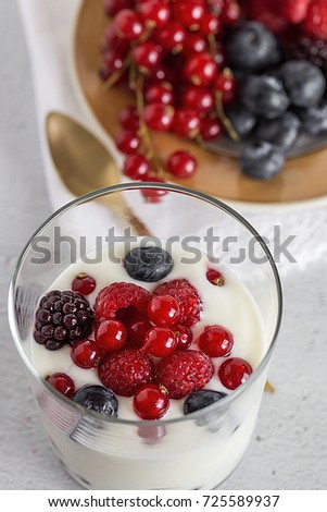 Yogurt with berries, blueberries and raspberries on wooden table. Healthy #725589937