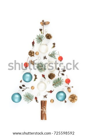 Christmas tree made of New year`s decorations, acorns, cones, spruce, apples, winter things on white background.  Holiday greeting card. Flat lay, minimal #725598592