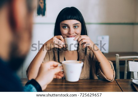 Happy romantic couple on date, drink warm coffee with milk, she looks lovingly at her boyfriend or partner, smiles and spark in her eyes. early morning family routine #725629657