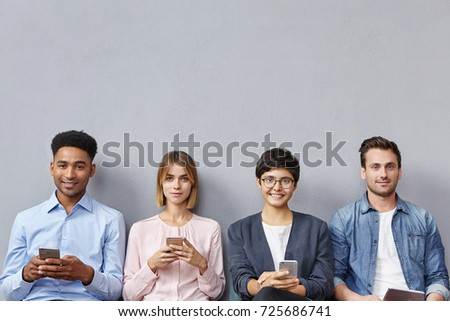 Group of friends or companions, meet together to discuss merging of companies, wait for one more partner, use modern gadgets, recieve messages or download pictures, isolated over grey background