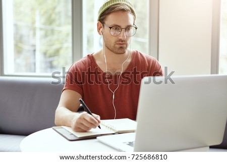 Concentrated bearded young European hipster in stylish round glasses and green hat looking at laptop screen and making notes in copybook while learning online, watching webinar using earplugs Royalty-Free Stock Photo #725686810