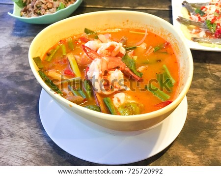 Tom Yum Goong Spicy Sour Soup on wooden table top view, Thai local food #725720992