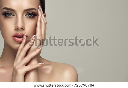 Beautiful model girl with a beige French manicure nail design with rhinestones . Fashion makeup and care for hands and nails and cosmetics . #725790784