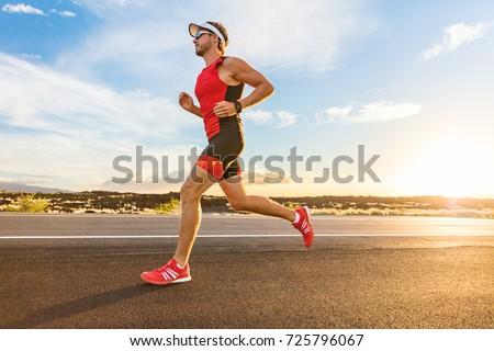 Triathlon - Triathlete man running in triathlon suit training for ironman race. Male runner exercising on Big Island Hawaii. Sunset. Royalty-Free Stock Photo #725796067