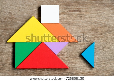 Colorful tangram puzzle in home shape wait for fulfill on wood background (Concept for build dream house, happy family life, property investment) #725808130