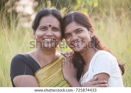 Portrait of happy mother and daughter in meadow at sunset. Smart Blurred photo #725874433
