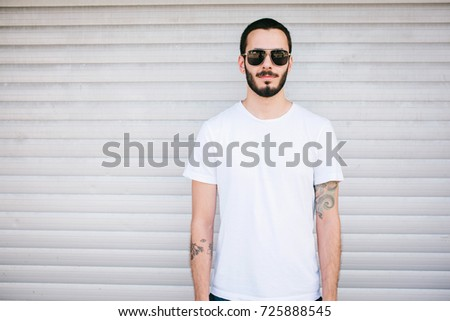 A young stylish man with a beard in a white T-shirt and glasses. Street photo #725888545