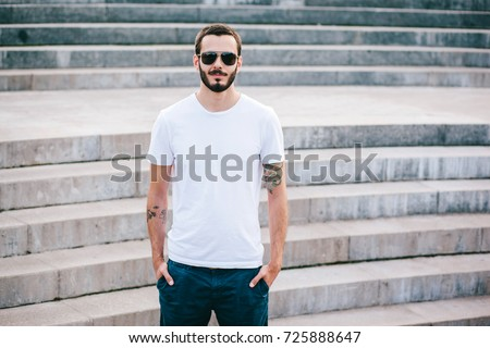 A young stylish man with a beard in a white T-shirt and glasses. Street photo #725888647