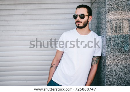 A young stylish man with a beard in a white T-shirt and glasses. Street photo #725888749