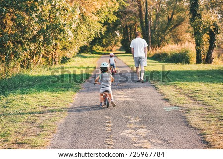 Family on a bicycle enjoying a family walk together outside on a path with golden leaves in an autumn park  #725967784