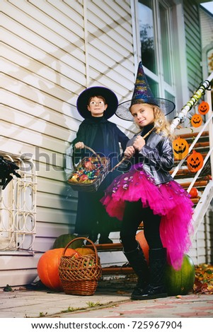 Happy children in a costumes of witches and wizards celebrating halloween. Trick or treat. Halloween party. #725967904