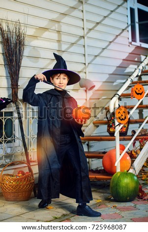 A boy in a costume of wizard with his magic wand is going to a halloween party. Trick or treat. Halloween concept.  #725968087