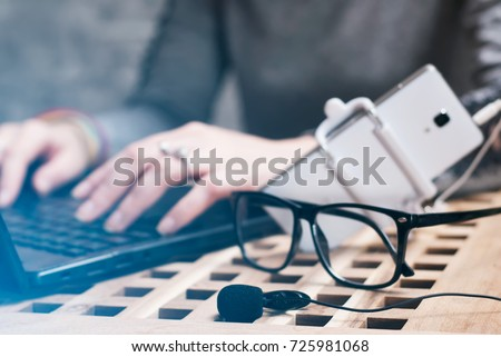Female blogger writes the text on the laptop. The set of objects for video blogging, lavalier microphone, smartphone, selfie stick