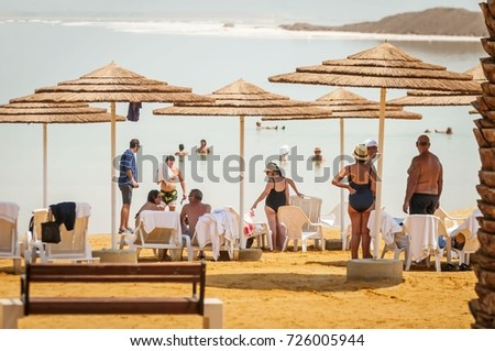 EIN BOKEK, ISRAEL. September 16, 2017. People enjoying the summer heat on the Dead sea shore and swimming in the salty water. #726005944