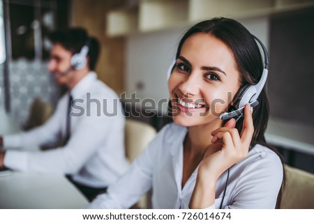 How can I help you? Beautiful call center workers in headphones are working at modern office. Royalty-Free Stock Photo #726014674