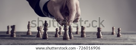 Wide cropped image of a human hand wearing business suit moving dark King chess piece at table, toned retro effect. #726016906