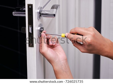 handyman repair the door lock in the room, Man fixing lock with screwdriver, Close-up of repairing door, professional locksmith installing or repairing a new deadbolt lock on a house #726025735