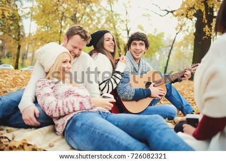 Friends having a good time in park at autumn/ singing and playing guitar  #726082321