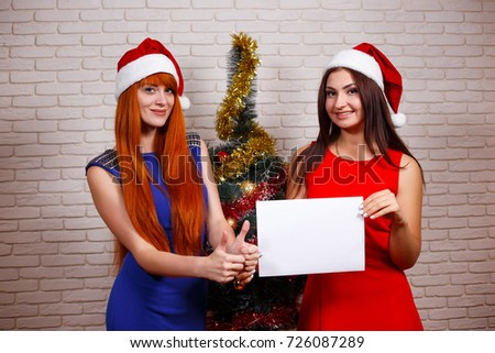 Two young beautiful women in Santa caps holding empty sheet of paper. Free space for advertisement or text, mockup for design.New Year, Christmas time gift concept #726087289
