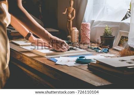 Beautiful woman hand crafting book at the tabletop with stationery. Stylish craftswoman with stationery work at his hipster workstation. Royalty-Free Stock Photo #726110104