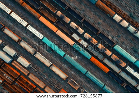 Aerial view of colorful freight trains on the railway station. Cargo trains close-up. Wagons with goods on railroad. Heavy industry. Industrial conceptual scene with trains. Top view. Vintage style #726155677