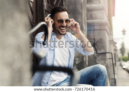Handsome attractive man listening music and singing in the street #726170416