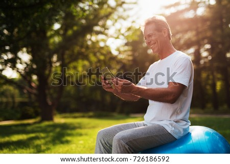 A man sits in a park on a blue bowl for yoga. He is looking at something on his gray tablet and smiling #726186592