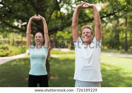 Couple doing exercises in the park. Man and woman doing exercises in the park. They warm up. They do stretching hands #726189229