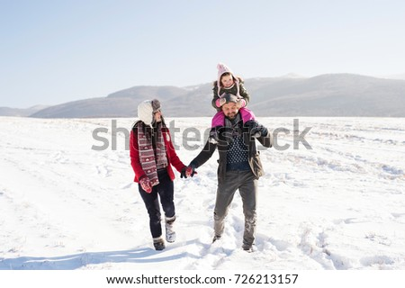 Father and mother with their daughter on a walk, winter nature. #726213157