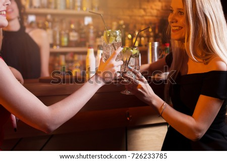 Two girlfriends having a night out toasting with glasses of mojito cocktail at bar #726233785
