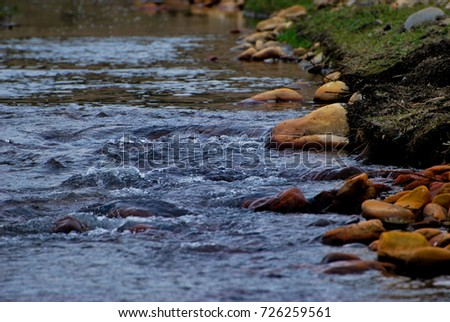 River in mountains with red stones in the water #726259561