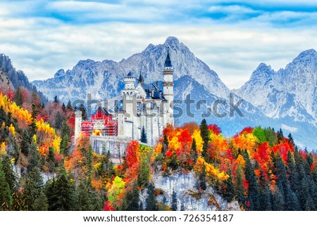 Neuschwanstein medieval castle in Germany, Bavaria land. Beautiful autumn scenery of Neuschwanstein ancient castle circled by colorful tree, amazing seasonal fall scene. Famous and popular landmark. Royalty-Free Stock Photo #726354187