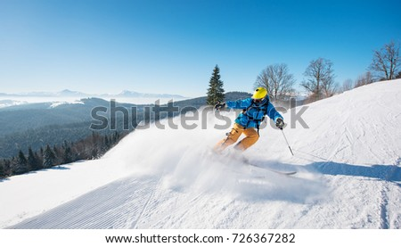 Shot of a professional skier riding the slope in a beautiful winter day copyspace ski resort recreation travelling tourism vacation extreme adrenaline #726367282