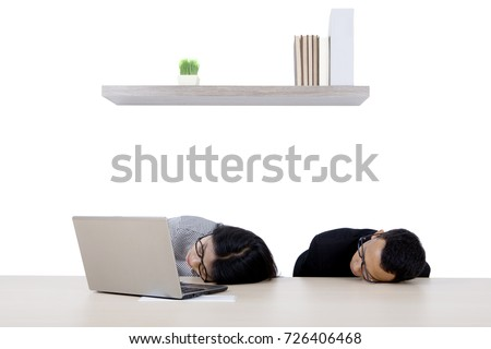 Two business people sleeping in the office while working with a computer laptop #726406468