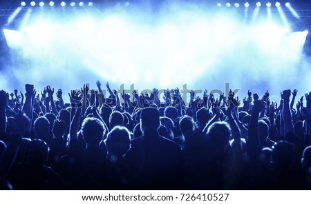cheering crowd at rock concert in front of bright lights #726410527
