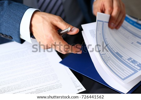 Male arm in suit offer insurance form clipped to pad and silver pen to sign closeup. Strike a bargain, driver money loss prevention, secure road trip, harmless drive idea, owner protective concept Royalty-Free Stock Photo #726441562