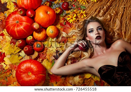 A beautiful young girl with long blond hair lies on maple leaves near apples and pumpkins.Autumn, holiday, abundance, natural, beauty, fashion, still life, postcard, picture.
