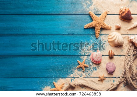 Summer time concept with sea shells and starfish on a blue wooden background and sand #726463858