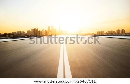 Highway overpass with modern city skyline background and evening sunlight #726487111