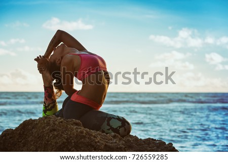 Young active woman sit in yoga pose on beach rock, stretching to keep fit and health.  #726559285