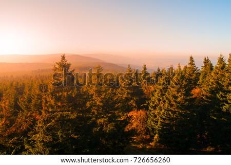 Autumn haze illuminated by sun above mountain peaks, Eagle Mountains, Orlicke hory, Czech Republic. #726656260