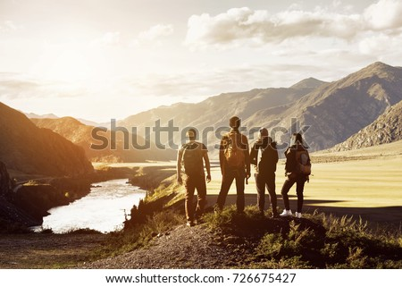 Group of four people stands on mountains and river backdrop. Travel expedition trekking concept with space for text Royalty-Free Stock Photo #726675427