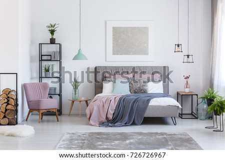 Comfortable powder pink chair next to shelf with firewood in soft pastel bedroom with decorative glass vases #726726967