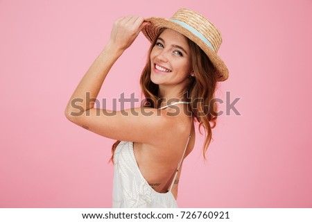 Portrait of a smiling attractive woman in summer dress and hat posing while standing and looking at camera isolated over pink background