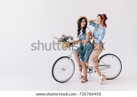 multicultural women in stylish retro clothing sitting on bicycle isolated on grey #726766450