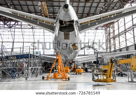 Large passenger aircraft on service in an aviation hangar rear view of the tail, on the auxiliary power unit Royalty-Free Stock Photo #726781549