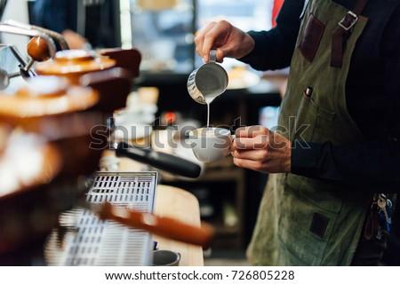 Barista making cappuccino, bartender preparing coffee drink  #726805228